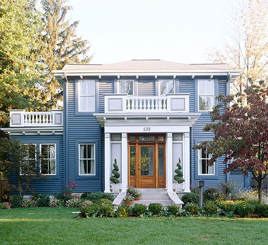 #10 After: Happy Home  Removing the slope-roofed porch, then centering the front door and surrounding it with a smaller, flat-roofed porch with side panels and pillars gives this home a happier exterior. Low-maintenance vinyl siding in ocean blue contrasts nicely with the wood door and white trim.