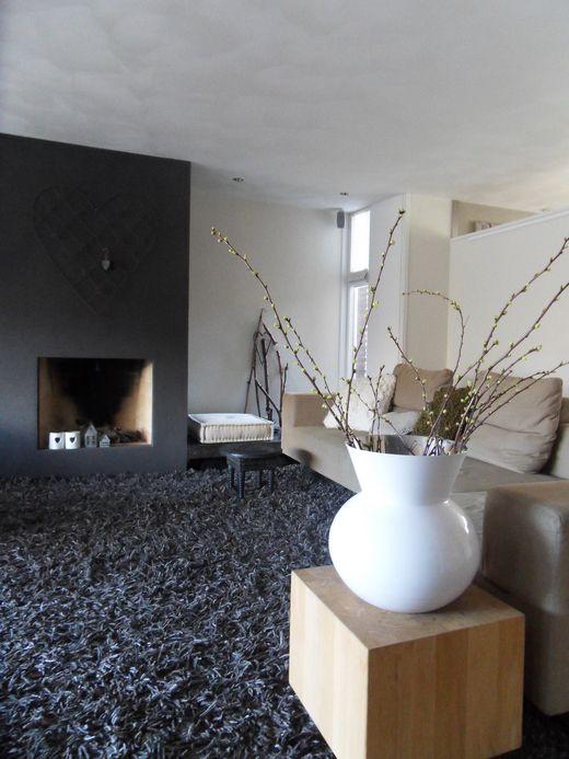 Een grote vaas met takken brengt de lente in huis. Het grove en grote karpet geeft een warme uitstraling aan het geheel.
