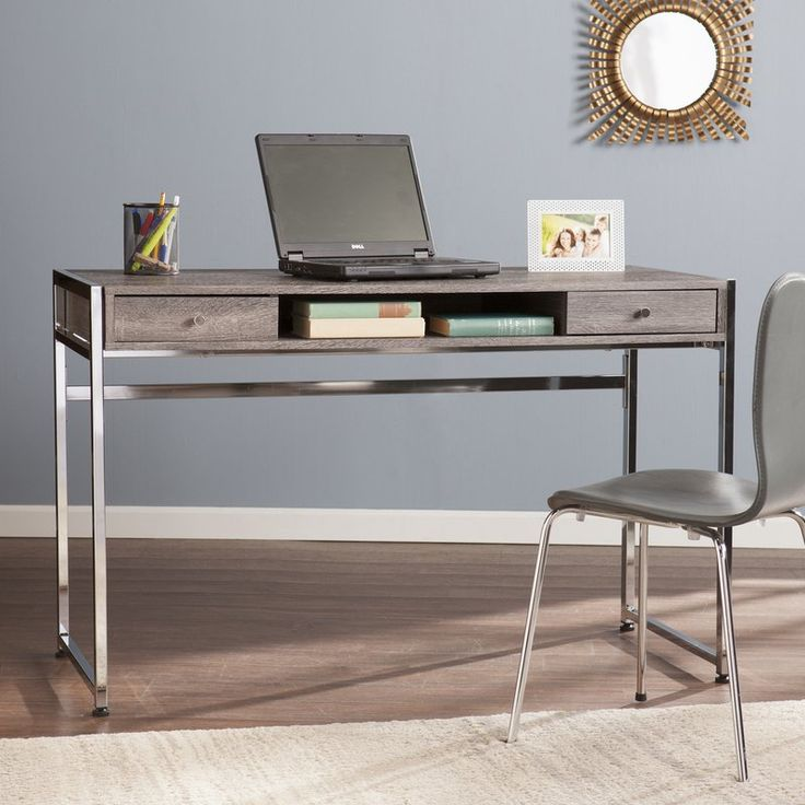 High function and style combine with this chic writing desk in a study, home office, or studio. Crisp chrome plated legs juxtapose with weathered gray for two-tone, mixed media bliss. Spacious desktop and wide clearance let you spread out or share your workspace. Broad shelf gives your laptop or tablet organized shelter; side drawers house writing utensils and small electronic accessories. Geometric architecture set a midcentury modern style scene with this sleek desk. Variations in scraping…
