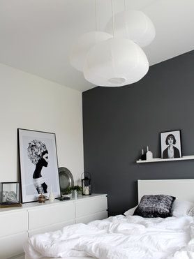 Black and white bedroom, with multiple round lamps and framed photo art in different sizes.