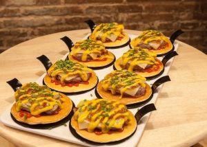 Blini met hamburger, kaas, gekarameliseerde ui, bieslook, ketchup en mosterd