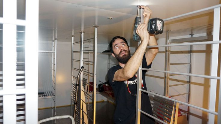 Tim Delay (France) installing shelving in the new freezer on Deck 6.