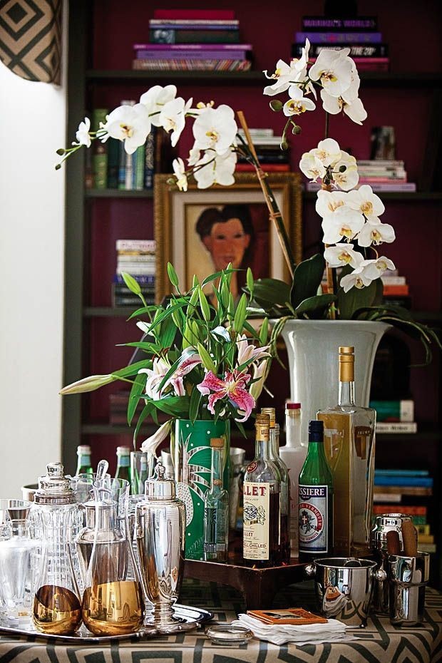 An elegant bar table set up. Orchid in vase, fresh cut stargazer lilly's, the bar essential' s in silver.