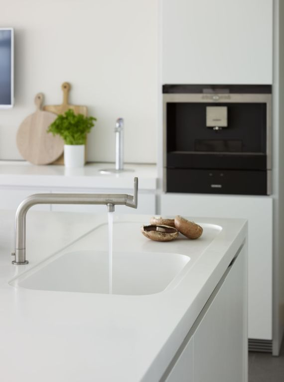 White corian worktop with moulded, integrated kitchen sink. The elegant kitchen tap by bulthaup suits this minimal white kitchen. Lympstone Project | Sapphire Spaces - bulthaup tap