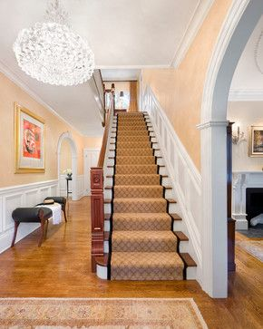 Eclectic foyer...contemporary chandelier, Moroccan newel post, white wainscoating, yellow walls, beige and black stair-runner, arched entryways.