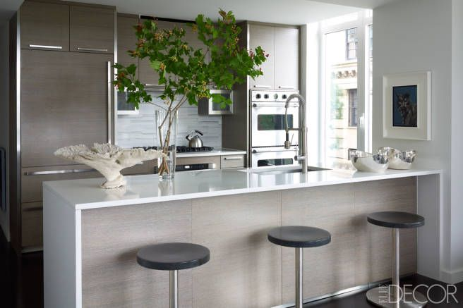 The kitchen's stools and quartzite countertops are custom designs, the backsplash is Cipollino marble, the double oven is by Viking, and the refrigerator is by Sub-Zero.