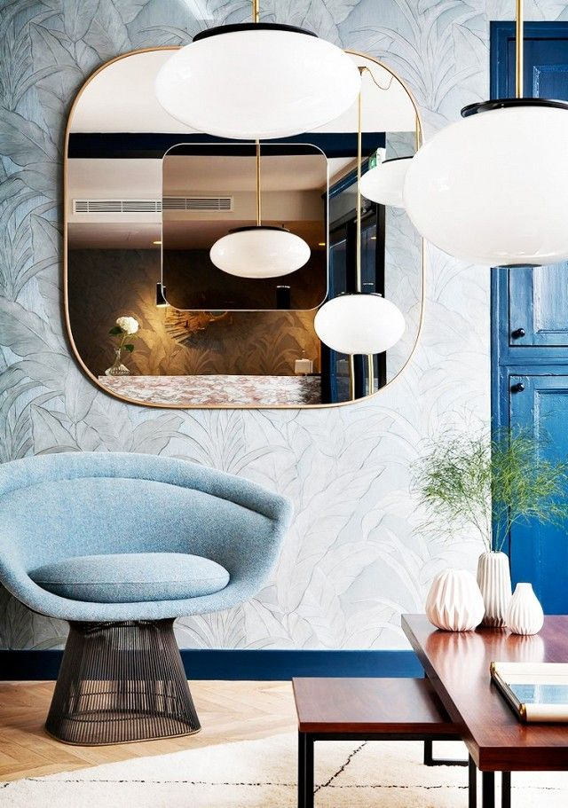 Hotel with wallpaper, a large gold mirror and a retro pendant light and a modern armchair