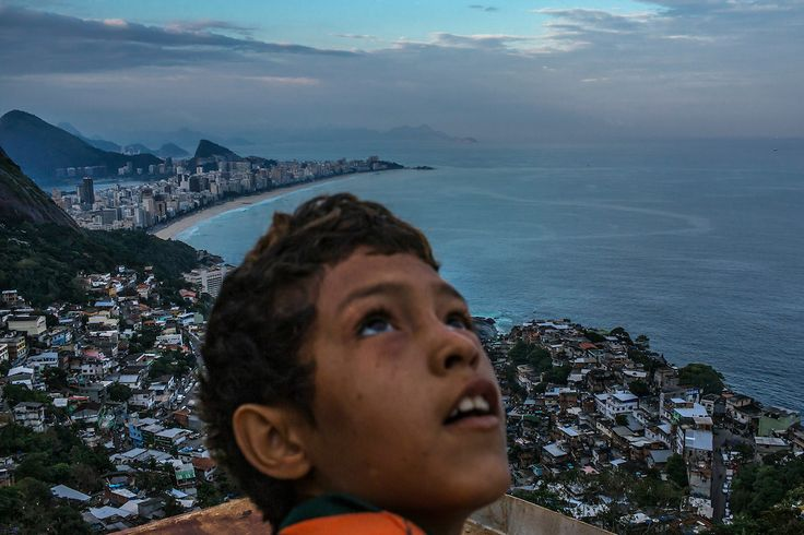 Rio de Janeiro, Brazil - June 15, 2013: A boy flies a kyte atop of a boutique hotel under construction at Vidigal hillside slum as Ipanema beach appears in the background. As cries of price gouging intensify just six months ahead of the start of the World Cup, with even modest hostels in Rio de Janeiro charging as much as $450 for a bed during the soccer tournament, the dwellers of Rocinha and other favelas are offering their own solution to Rio's acute shortage of hotel rooms: renting out…
