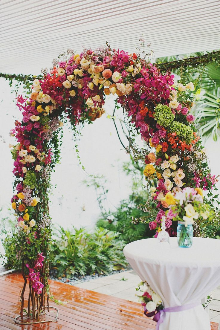 Colorful wedding floral arch with lavender, lilac and orange blooms | A Vintage Garden Wedding at The White Rabbit: Julien + Theora