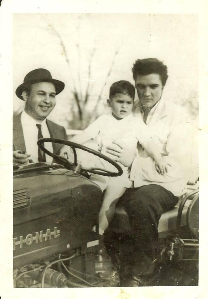 "Bo Wimmer‎ who uploaded this rare picture into the ELVIS PICTURES group on fb wrote:""This photo was left to me by my family...I have no idea who the child is. If anyone does know positively who the other people are, would love to know."" Taken at Graceland on Good Friday, April 19, 1957, the day Elvis's Easter guest Yvonne Lime had a photo shoot with Elvis. There were photos of other kids taken on that day too with Elvis on the tractor. Graceland was then still being refurbished."