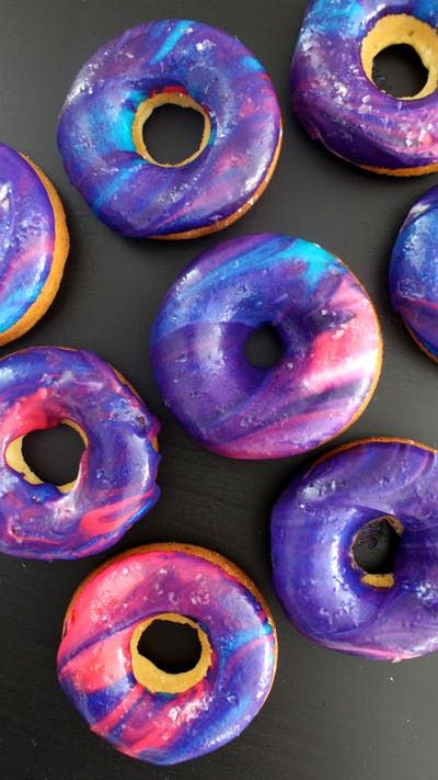Recipe with video instructions: Donuts as beautiful as the night sky — and they're delicious too! Ingredients: 1/3 cup + 1 tbsp milk, 1 tsp white vinegar, 3 tbsp unsalted butter, melted, 1 cup all-purpose flour, 1 tsp baking powder, 1/4 tsp salt, 1/4 cup sugar 2 tbsp honey, 1 large egg, 1/2 tsp vanilla extract, 3 tbsp whipping cream (plus a little extra, if needed), 1 tsp vanilla extract, 1 cup confectioner's sugar, pink, purple and blue food coloring, edible glitter