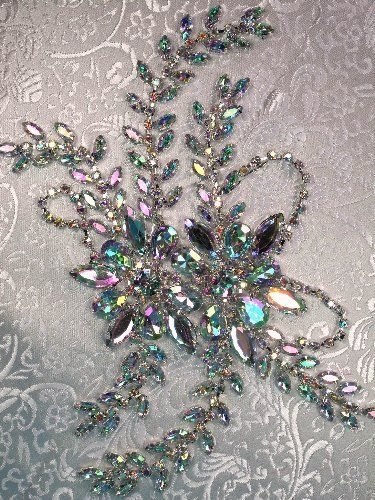 """The lovely and eye-catching XR83 CAB Crystal Aurora Borealis Rhinestone Applique Embellishment measures 9"""" x 4.5"""", and is sure to draw attention and compliments your way! A very flexible applique, the backing can be bent and turned in many ways, making this a great choice among larger embellishments. A stunning Victorian floral design with leaves trailing out from the center, this piece is accented with our fabulous Aurora Borealis stones, with some high quality acrylic rhinestones"""