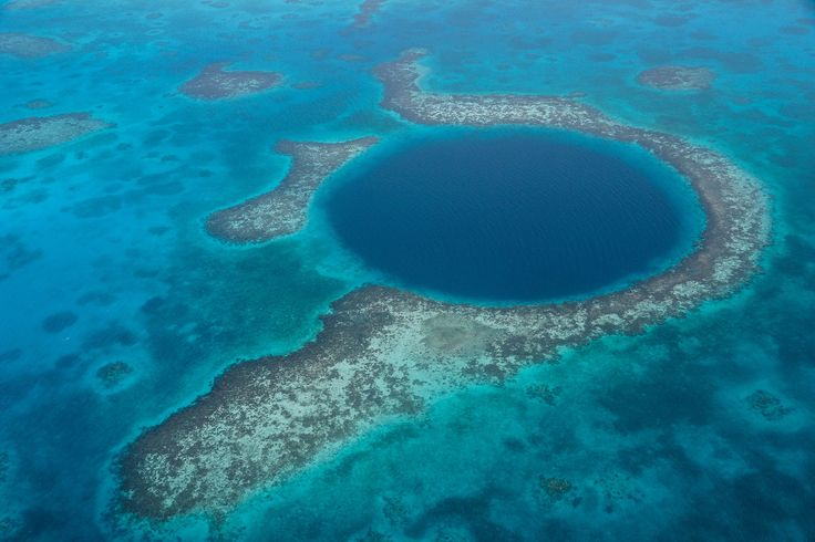The Great Blue Hole is a huge submarine sinkhole off the coast of Belize that Jacques Cousteau named one of the top scuba diving sites in the world.