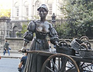 """This sculpture nicknamed by Dubliners """"Tart with the cart"""". Statue of Molly Malone in seventeenth-century dress by Jeanne Rynhart, Grafton Street, Dublin. Follow link for interesting article by Sean Murphy last updated 16 May 2013"""