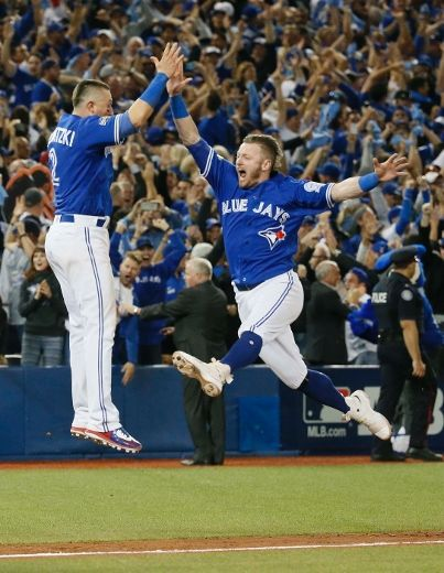 Troy Tulowitzki and Josh Donaldson celebrate the Toronto Blue Jays extra innings walk-off Wild Card victory over the Baltimore Orioles, advancing to the ALDS against the Texas Rangers. 2016 Postseason. MLB. Baseball. Photo credit Toronto Sun Stan Behal Jack Boland.