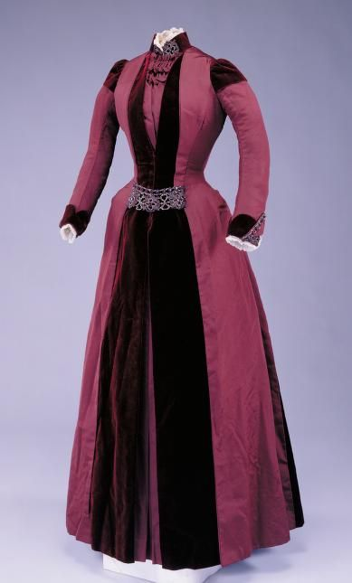 This dress, made of maroon velvet and ribbed silk, was purchased in 1888 by Mrs. Joseph Wells Stevens.  By this time, the bustle had all but disappeared. In this case only a vestigial bustle remains, built-in to the lower back area of the separate petticoat to provide skirt fullness. There is no waist seam; instead the fit is achieved through a princess line silhouette, with vertical seams piecing eight separate pieces make up the bodice, a testimony to intricate tailoring.