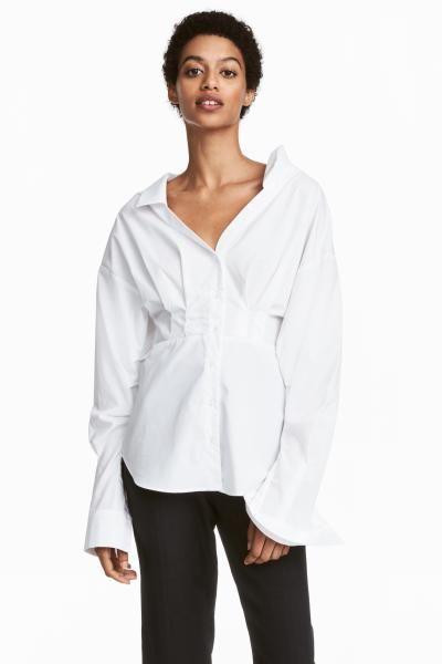 コットン織物素材のVネックブラウス。襟付きで、フロントボタン。胸元はルーズフィットで、プリーツが入っています。ウエスト部分の切り替えに向かって細くなるシルエット。ドロップショルダー。ボタン留めのカフスが付いた長袖。袖下のシームにギャザーが施されています。