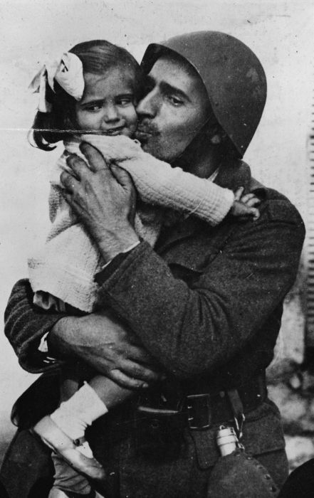 A Greek soldier holding his little daughter in his arms