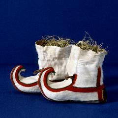 This pair of Sami baptismal boots belonged to a girl in a nomadic Sami family who followed their grazing reindeer flocks. The boots are made of white fur from a reindeer calf, and this is considered the finest quality fur.