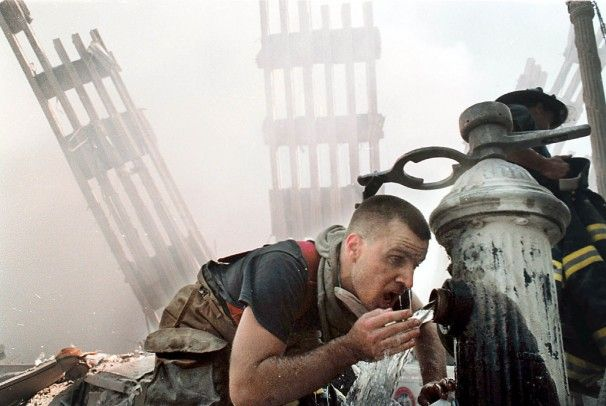 U.S. Customs Volunteer Firefighter Michael Saber drinks water from a fire hydrant in the rubble of the World Trade Center towers.