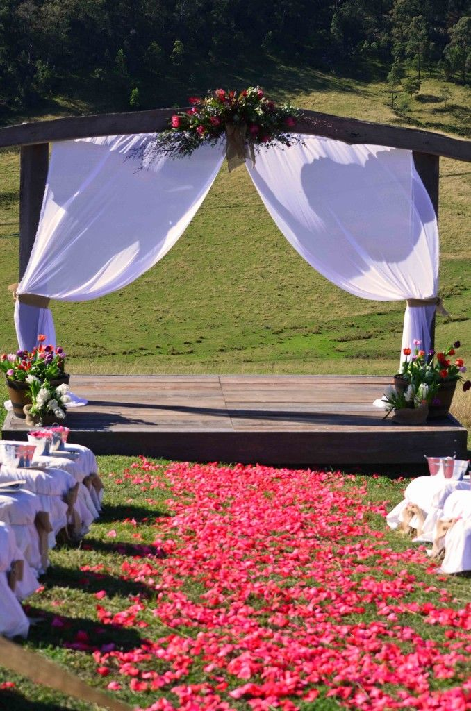Red Rose petals leading to rustic timber archway. Authentic Australian Wedding location, near Sydney, NSW. http://www.chapmanvalleyhorseriding.com/country-australian-wedding-part-1/   Bride and Groom. Wedding Ceremony. Wedding Ideas. Rustic wedding. Outdoor wedding. Archway,  native flowers. Country wedding venue. Australian wedding venue. Timber. Wedding Ideas. Haybales for seats.