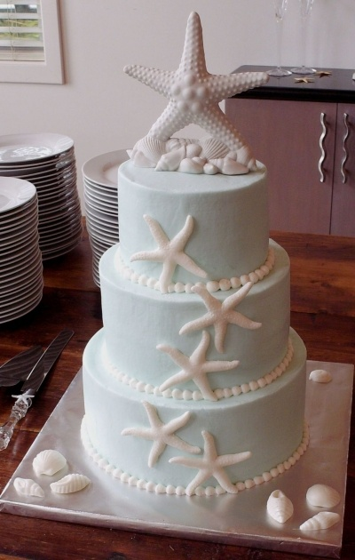 Beach Theme Wedding-My friend Penny's daughters had a similar one but her's had crushed graham cracker crumbs around the base of the cake to look like sand and a few of the shells were molded white and light brown chocolate swirled to look like marble.