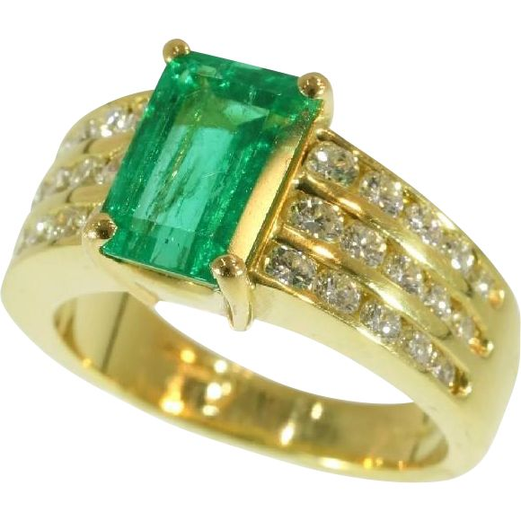 A fine ring c.1986 by Kutchinsky in 18 karat yellow gold, British hallmarks and Kutchinsky monogram, set with a center natural emerald 2.33 carat and