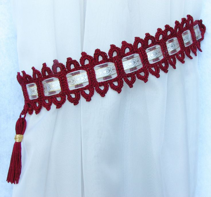 Burgundy fringed curtain tie backs with ribbon.