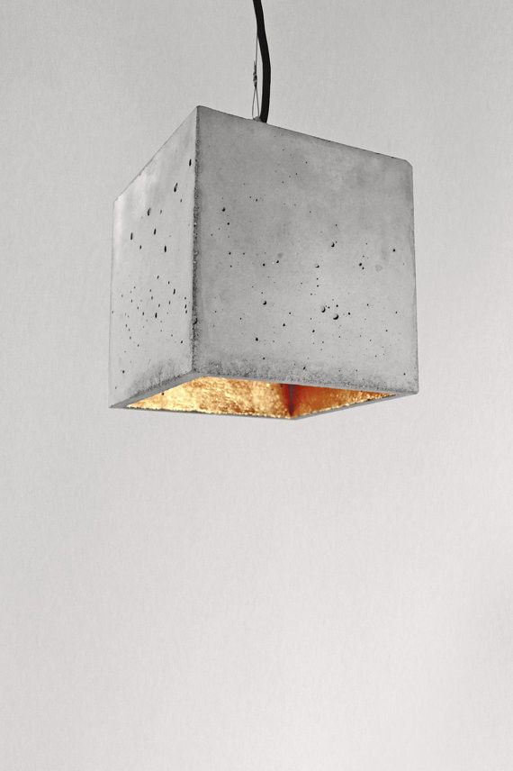 [ B5 ] The cubic hanging lamp [ B5 ] is cast from a light gray concrete. It combines noble gold with rough concrete into a timeless and elegant designer lamp . The high quality gilding the insides of