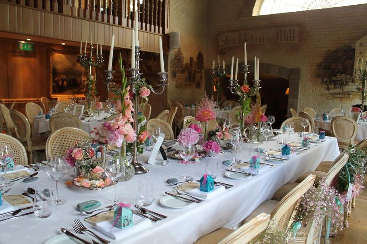 Top Table with candelabras and silverwear dressed with pink and coral flowers