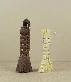 A choice of two whisk like brushes, one of straw coloured tampico, the other deep umber shuro. The p..