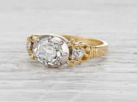 Antique Georgian engagement ring centering an old mine-cut cushion-cut diamond weighing approximately 0.85 carat with EGL certificate stating the diamond is H-I color/SI3 clarity. Setin 18K yellow gold and silver.Circa 1830. Shown with our Zephyr band. Don't let the breathtaking east-west set oval shape diamond take all the credit, this ring has a delicate scroll work band too. Diamond and gold mining has caused devastation in areas such as Africa, wreaking havoc on delicate ecosystem...