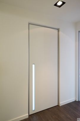 Moderne witte maatwerk blokdeur met verticale inbouwgreep en plexi