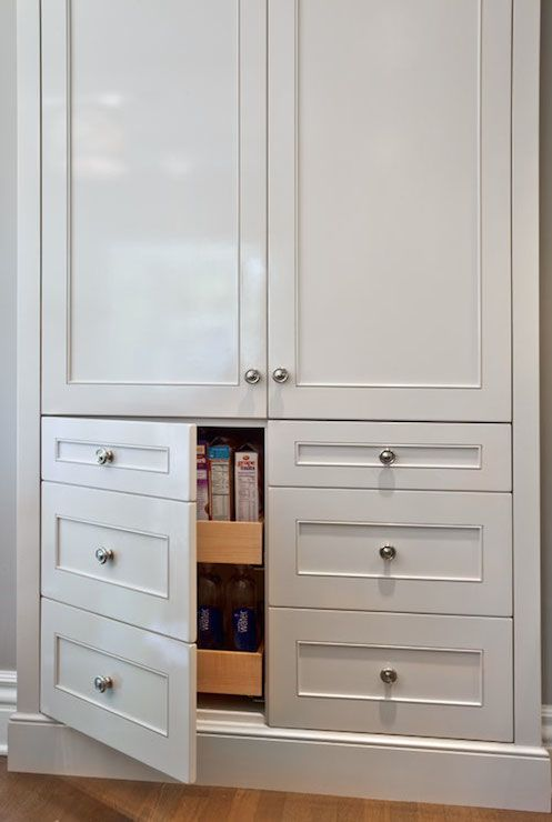Lovely kitchen features built-in pantry cabinets stacked over cabinet doors disguised as drawers opening to reveal pull-out pantry shelves.