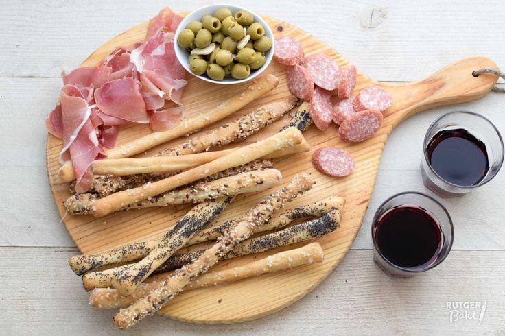 In Italië heten ze grissini, in Engeland bread sticks en in Nederland kennen we ze als soepstengels of broodstengels. Hoe je het ook noemt, lekker is het zeker! Ik serveer ze graag bij een borrelplank of natuurlijk bij een kop soep. Je kunt niet alleen met de topping, maar ook met het deeg zelf variëren. Kneed bijvoorbeeld eens wat kruiden of stukjes olijf door het brooddeeg.  Ingrediënten Voor het deeg 500 gr bloem 7 gr gedroogde gist 300 ml water, lauwwarm 50 ml olijfolie 10 gr zout…