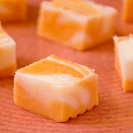 Orange Dream Fudge...3/4 cup butter,  3 cups sugar, 3/4 cup heavy whipping cream, 1 (10-12 oz) package vanilla or white chips, 1 (7 oz) jar marshmallow crème, 1Tbsp orange extract, 12 drops yellow food coloring, 5 drops red food coloring...