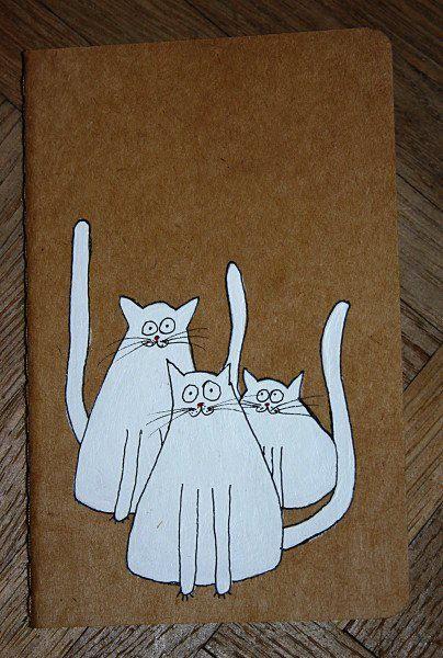 3 chats sur un carnet, carton souple, acrylique vinylique et encre de chine, 2010 © Astrid Genette