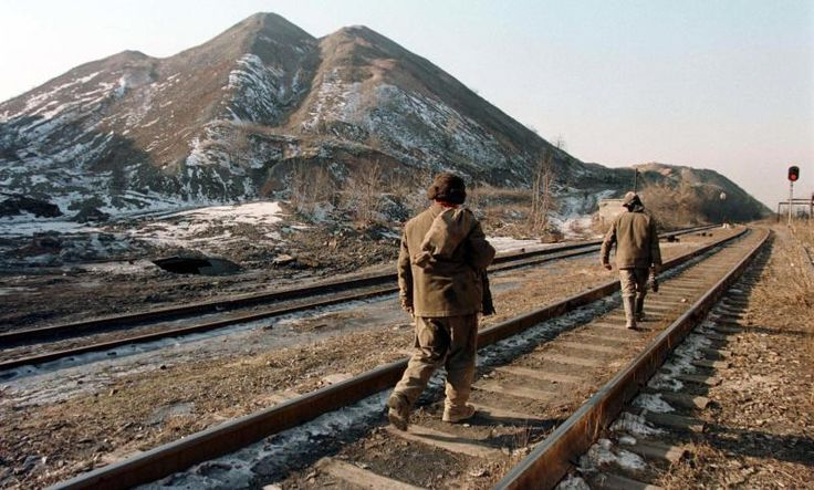 Miners walk along a railway at Panfilovskaya mine in the Donetsk region, 1998.
