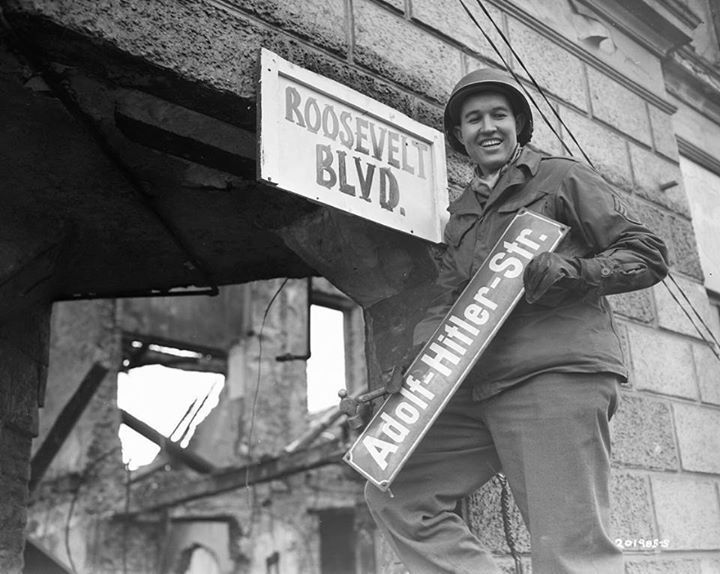 The denazification program in Germany mandated the elimination of Nazi names from public squares city streets and other venues. US Soviet and British soldiers enthusiastically removed Nazi emblems and renamed public spaces. Krefeld Germany March 9 1945. Credit: National Archives and Records Administration College Park MD.