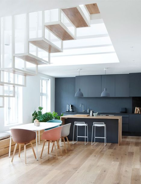 netural chairs contrast a dark charcoal grey kitchen // Floating steel staircase divides Haptic's Idunsgate Apartment in Oslo