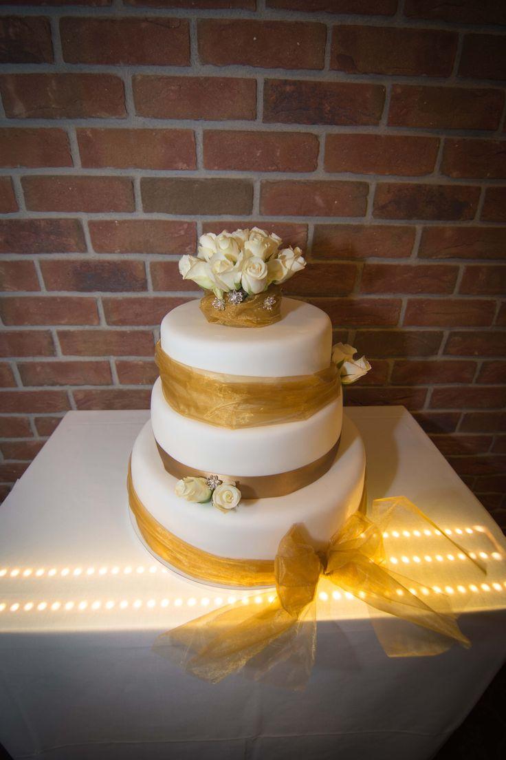 Třípatrový svatební dort, potažený fondánem a dozdoben organzou s živými květy.