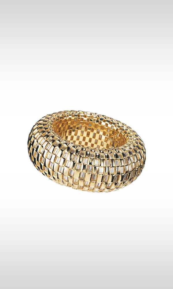 The Wheel, 1998: a round bracelet in yellow gold illuminated by 380 baguette-cut diamonds totaling 42 carats. This is an essential and modern design, a decorative motif that recalls a chessboard, alternating gold and diamonds, for a soft, perfect creation.