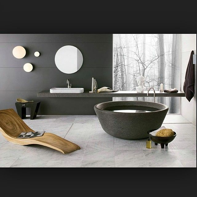 Round black stone freestanding bathtub, timber carved sledge chair, floating black polished concrete vanity, white bench mounted basin, chrome tap and mixer, round mirror. #taps #interiordesign #bathroom #australia #architecture #bathroomdesign #bathroomcollective Visit our website for more www.bathroomcollective.com.au