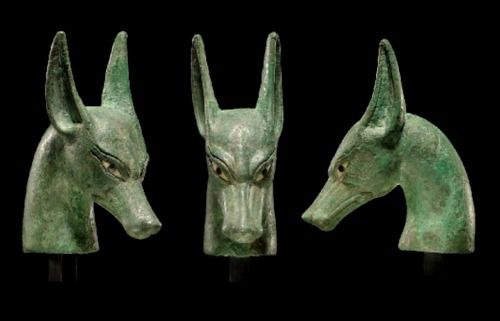 Egyptian Bronze Scepter Finial, New Kingdom, Dynasty XIX, 1307-1196 BC Cast in the form of a jackal head, the eyes inlaid in obsidian and white stone, presumably limestone.