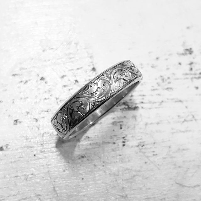 Some hand engraving in progress on a ring. A repeating scroll pattern working it's way around the whole ring.   #custom #handengraved #engraving #weddingring #bespoke