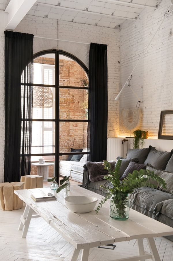 white painted chevron floor + huge white coffee table + painted white brick + gray sofa + black curtains + arched window