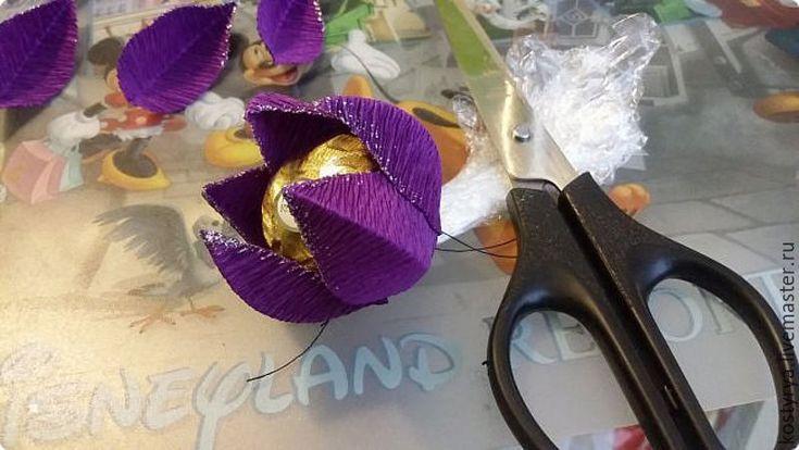 Мне в голову однажды пришла идея, а что если лепесток для цветка из гофробумаги сгибать поперёк направления складок у гофробумаги? И вот что получилось А сейчас я всё подробно расскажу как его сделать. Нам потребуется: - итальянска гофробумага; - горячий клей; - ножницы; - линейка; - пищевая плёнка; - нитки; - акриловая краска с блестками (для украшения — не обязательно); - конфетка.