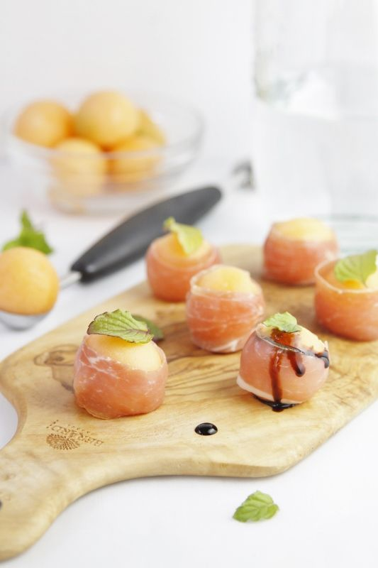 Prosciutto Wrapped Melon Balls topped with mint leaves and a drizzle of Balsamic Glaze