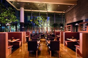 A dining room with trees, booths and a tables for two - The Ritz-Carlton, Los Angeles  | CA 90015