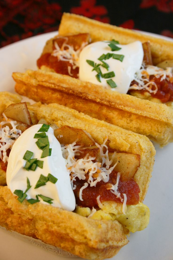 Huevos Rancheros Waffle Tacos Recipe _ *Place cooked waffle in taco holder *Add scrambled eggs or fried egg to inside of cornbread waffle *Put fried potato on top of egg *Add shredded cheese *Top with salsa & sour cream!